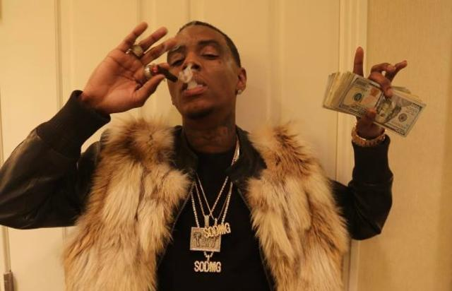 Soulja Boy smokes and holds a wad of money.