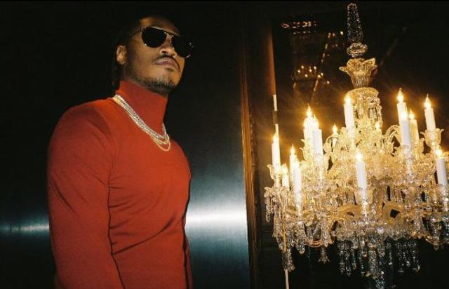 Future poses next to a chandelier.