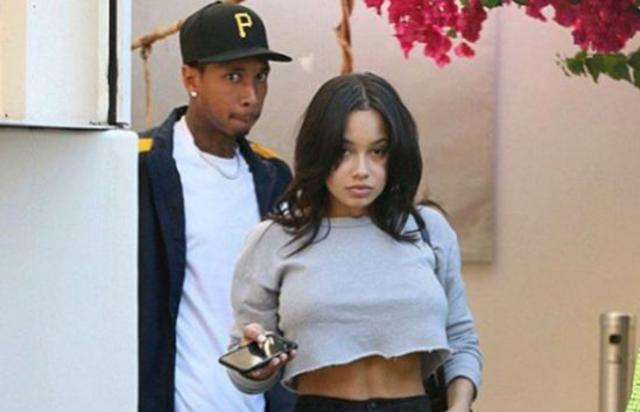 Tyga and a mystery woman walk out of a restaurant together.