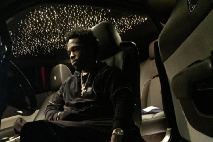 Curren$y lounging in a car.