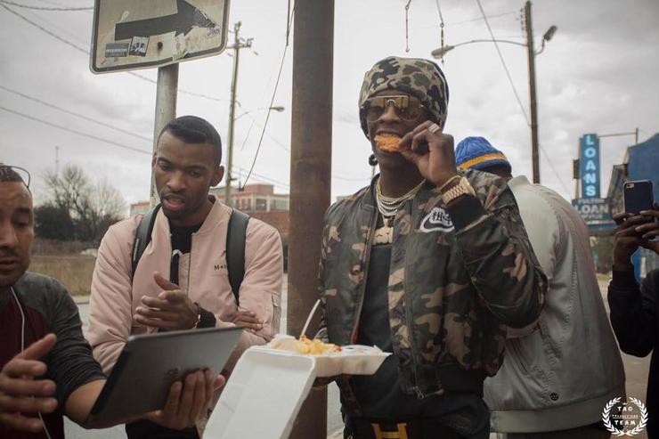 Young Thug eating a piece of chicken