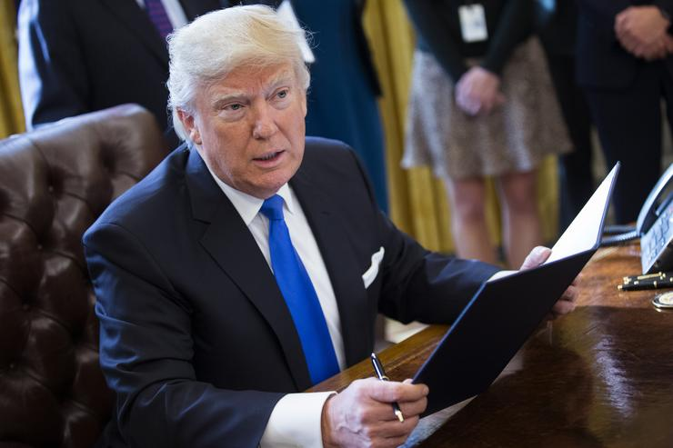 Trump signing executive orders in the oval office.