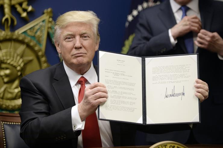 Donald Trump signing executive orders on Immigration and military reform.