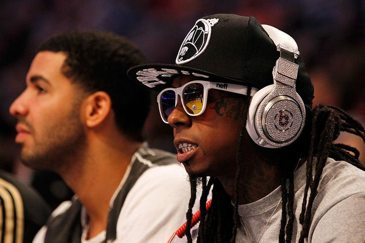 Lil' Wayne, wearing diamond studded beats headphones by Dr. Dre and Drake (L) sit courtside during the 2012 NBA All-Star Game at the Amway Center on February 26, 2012 in Orlando, Florida.
