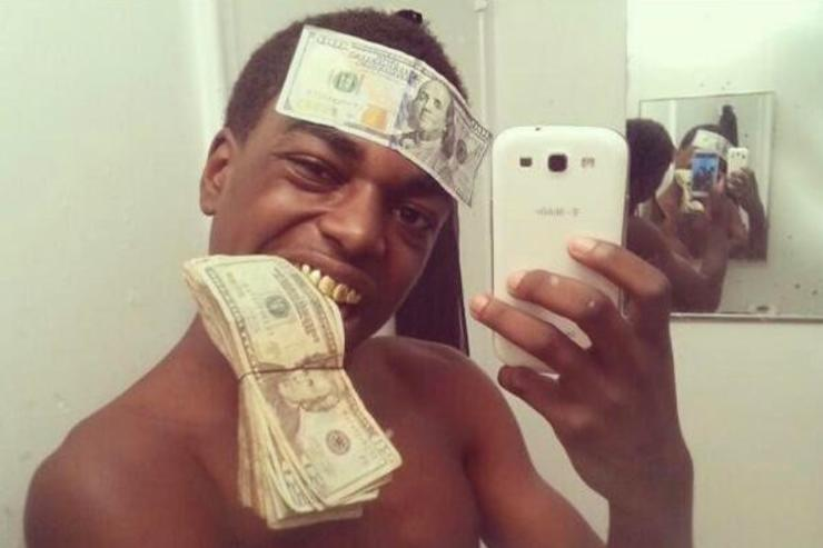 Kodak Black poses for a photo with dollars bills stuck to his forehead and in his mouth.