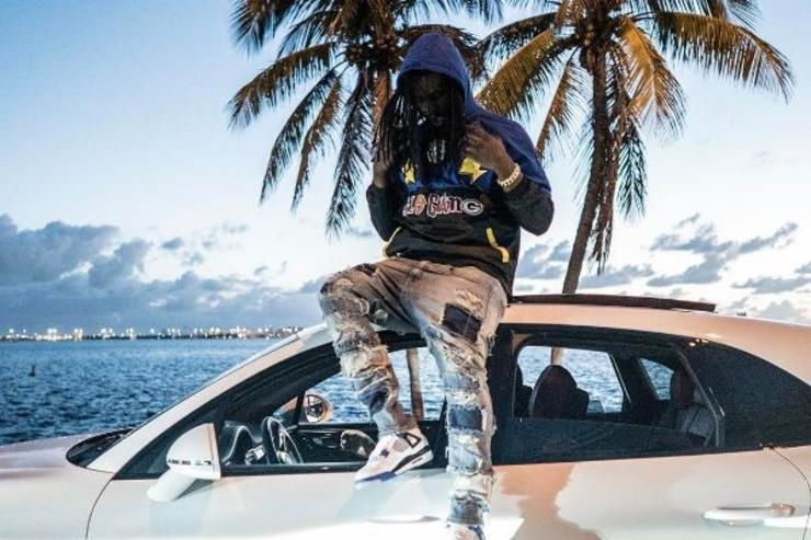 Chief Keef sits on the hood of a car.