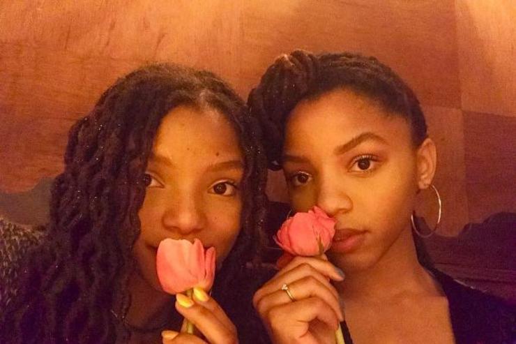 Chloe and Halle smell flowers.