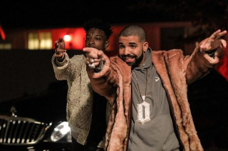 Drake and 21 Savage point at something off camera.