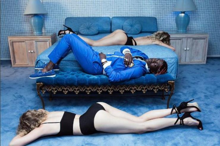 Lil Yachty reclines alongside two models.
