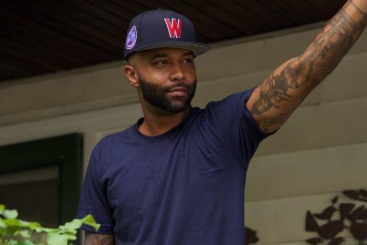 Joe Budden hangs out on a porch.