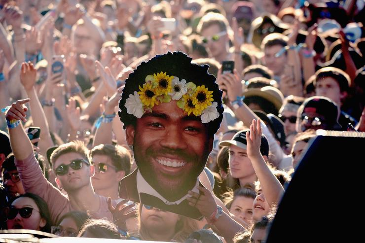 Festivalgoers hold up a cut out of Childish Gambino wearing a flower crown