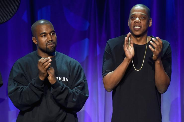 Kanye West (L) and JAY-Z onstage at the Tidal launch event #TIDALforALL
